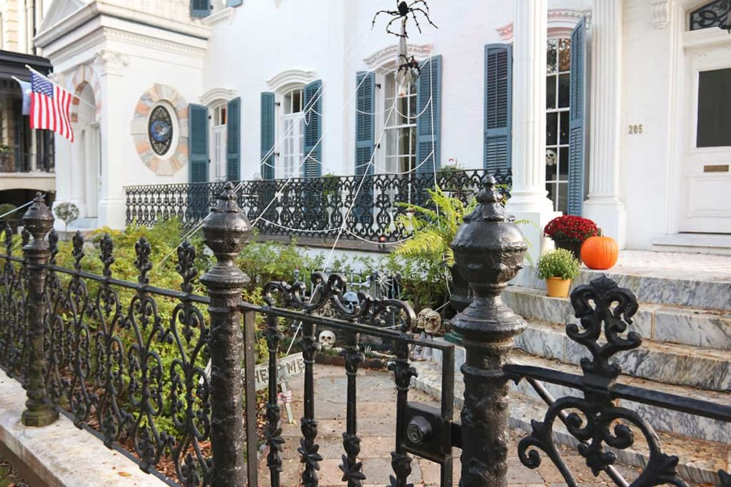 Multi-story white mansion in Savannah with a giant spiderweb and spooky Halloween decor