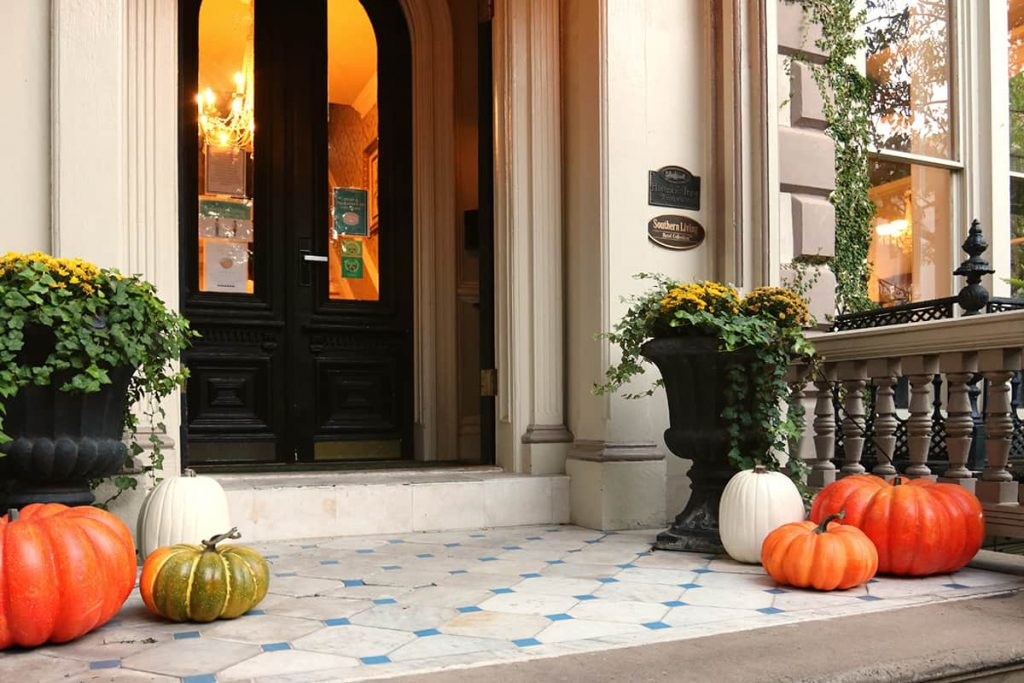 Front porch of an elegant mansion decorated with pumpkins and fall decor