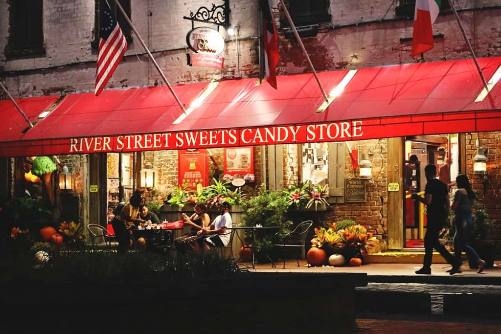 Exterior of River Street Sweets with the red awning lit up at night and pumpkins and fall decor by the door