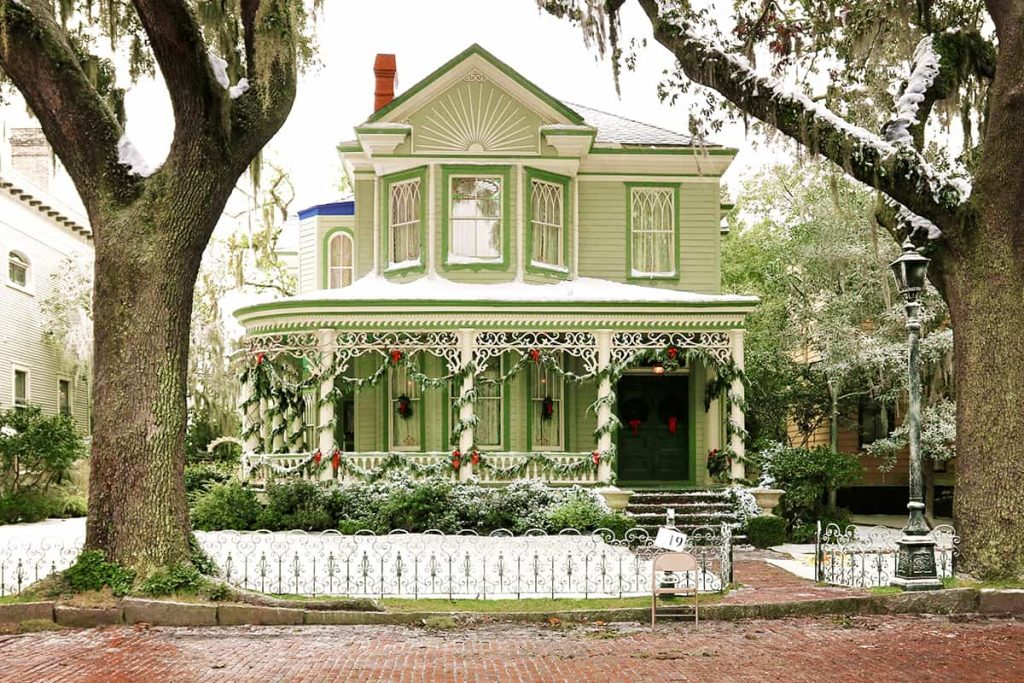 Green two-story Victorian home in Savannah decorated for Christmas with snow covering the front yard and roof