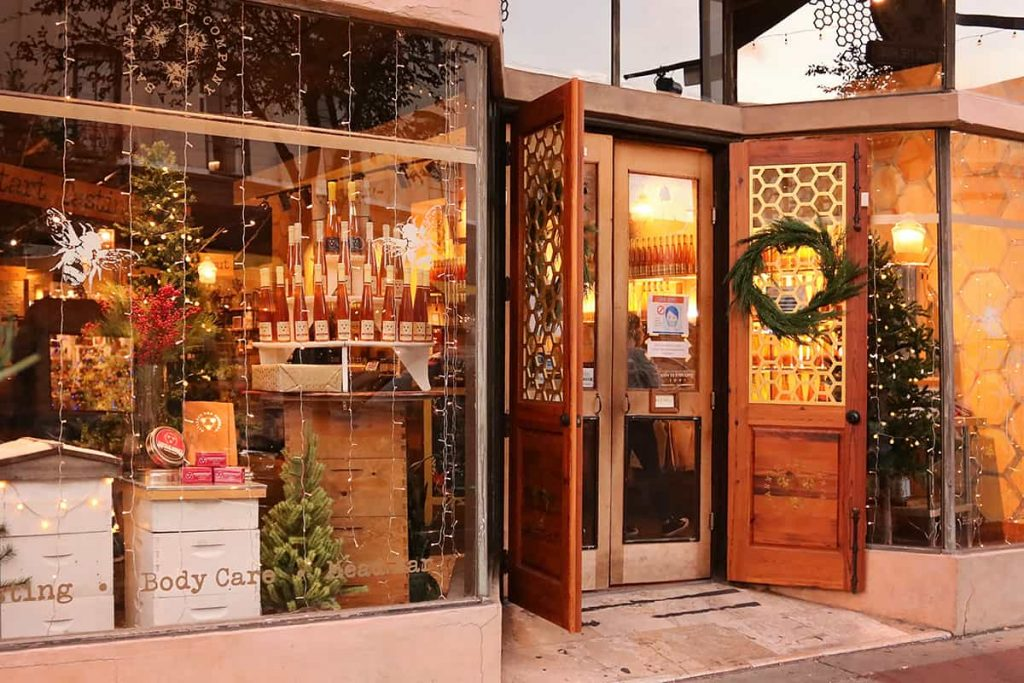 The Savannah Bee Company storefront with a Christmas wreath on the front door and Christmas trees in the window