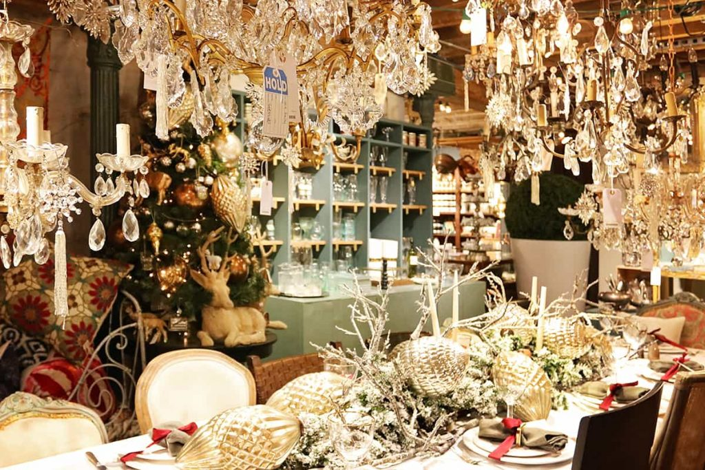 Elaborate silver ornaments as a centerpiece on a table display in The Paris Market with chandeliers hanging overhead and a Christmas tree in the background