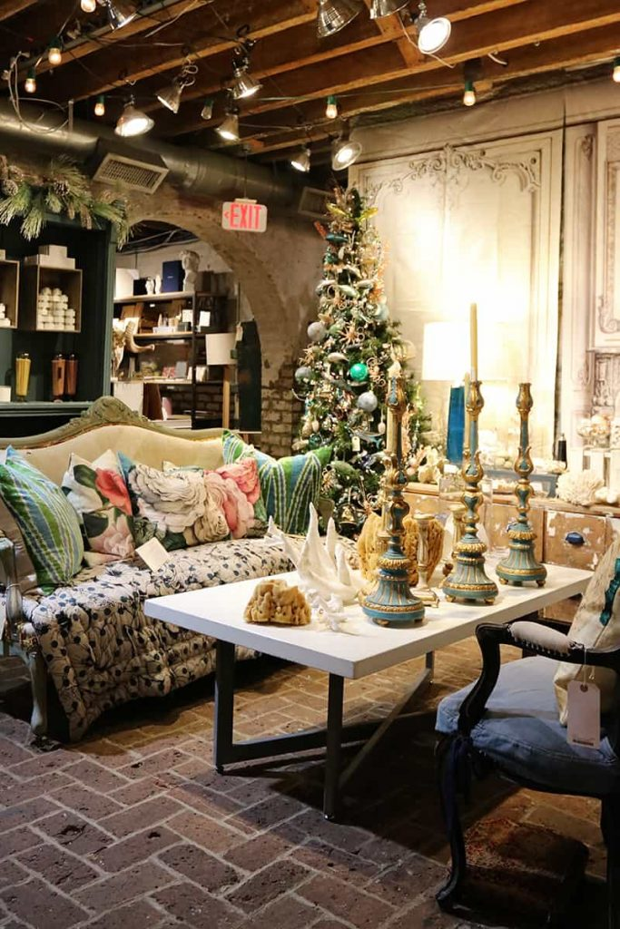 Display area in The Paris Market with a couch with colorful blue and green decorative pillows and a matching Christmas tree in the background