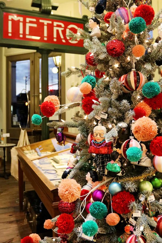 Christmas tree inside The Paris Market with colorful red, peach, and teal fluff ball decor and a Paris Metro sign in the background