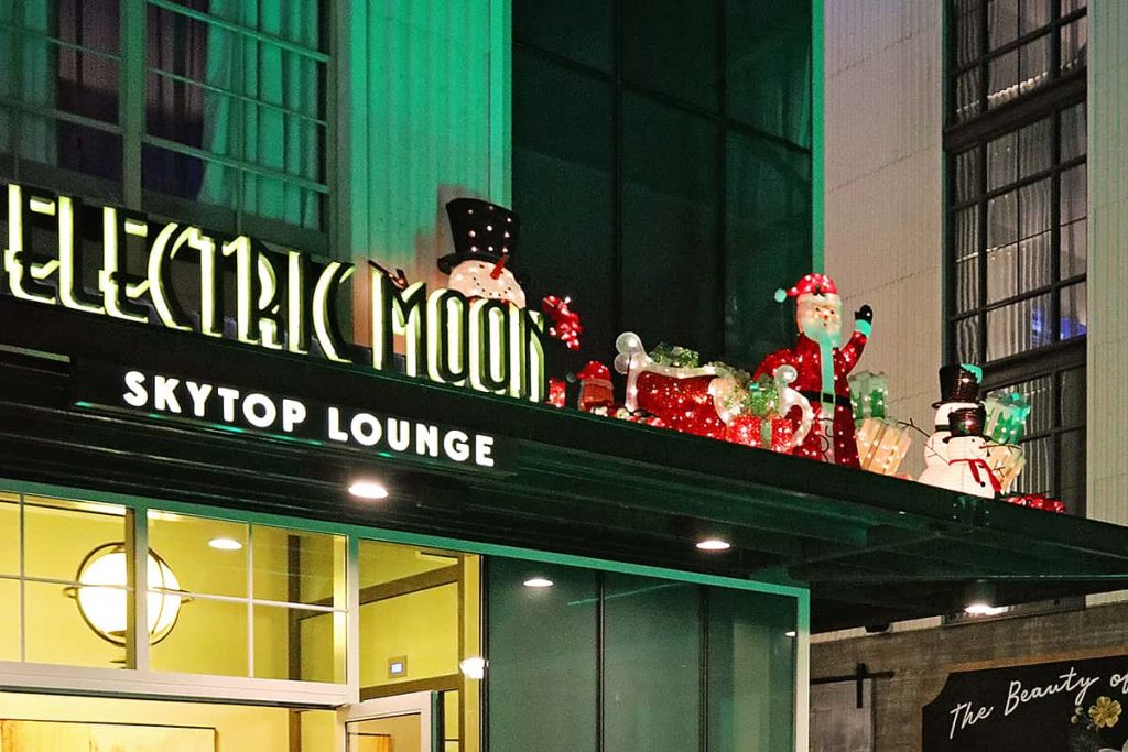 Neon signage reading Electric Moon Skytop Lounge with Christmas decor surrounding it