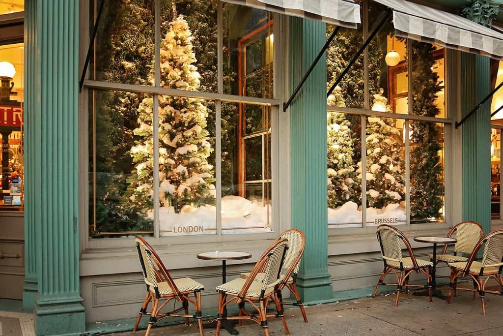 Elaborate holiday window displays of flocked Christmas trees at The Paris Market with cafe seating under a striped awning