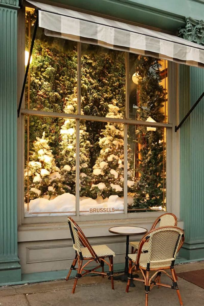 Elaborate holiday window display of Christmas trees at The Paris Market with cafe seating under a striped awning