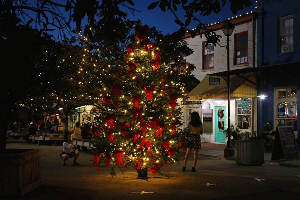 Christmas tree with white lights and red ribbons in the center of City Market in Savannah