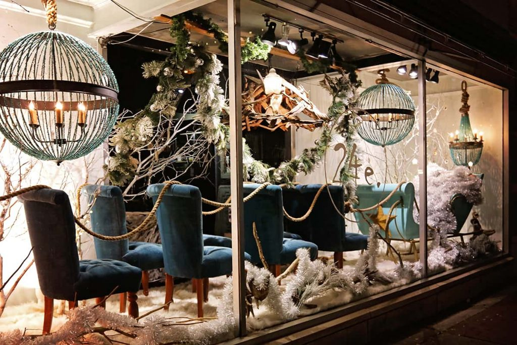 It's Christmas in Savannah at 24e furniture store with an elegant window display showing blue upholstered dining room chairs behind Santa's sleigh