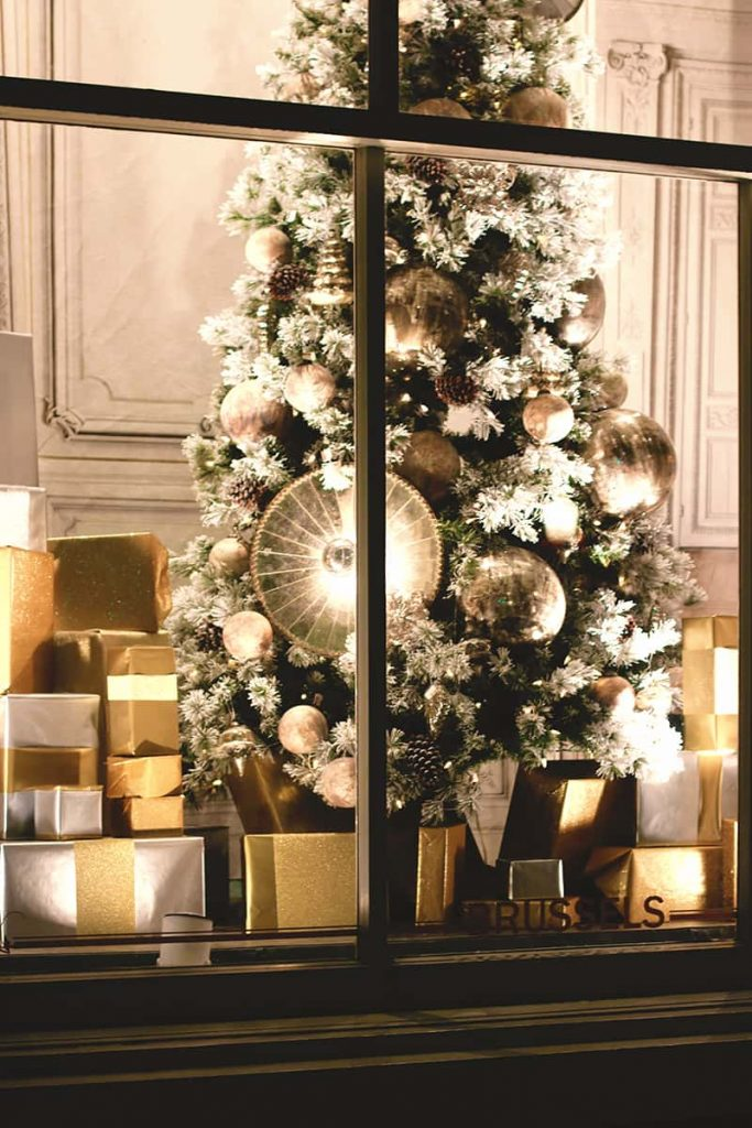 Elegant window display showing a Christmas tree with gold and white decorations