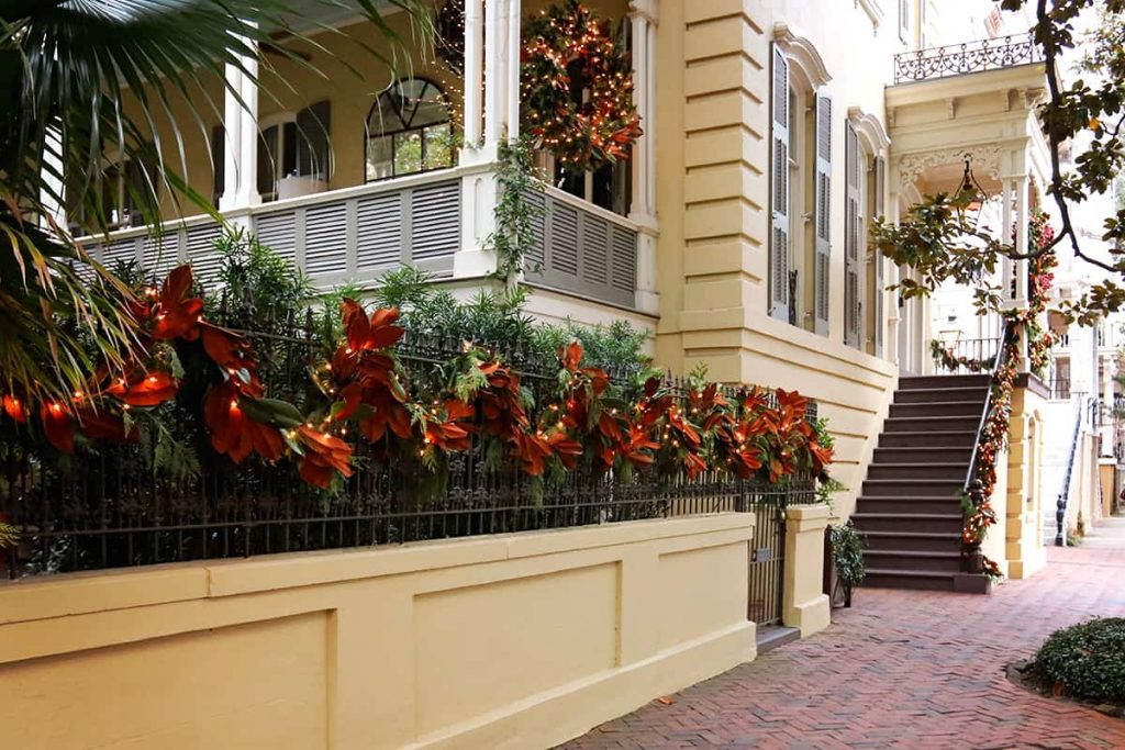 Yellow historic home with a large side porch and magnolia leaf Christmas decorations on the wrought iron fence