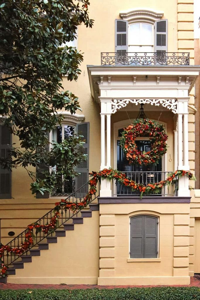 Christmas in Savannah with decorations on a yellow house with a second story porch that has detailed white Victorian-style trim
