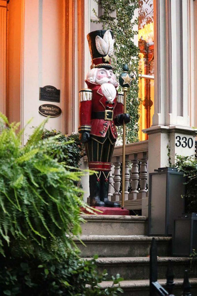 Street view of an oversized nutcracker guarding the door of the Hamilton-Turner Inn in Savannah