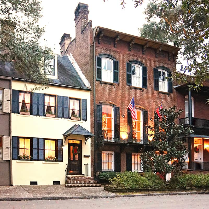 Street scene of two Colonial-style homes with candles and Christmas trees in the windows and Christmas wreaths on the front doors.