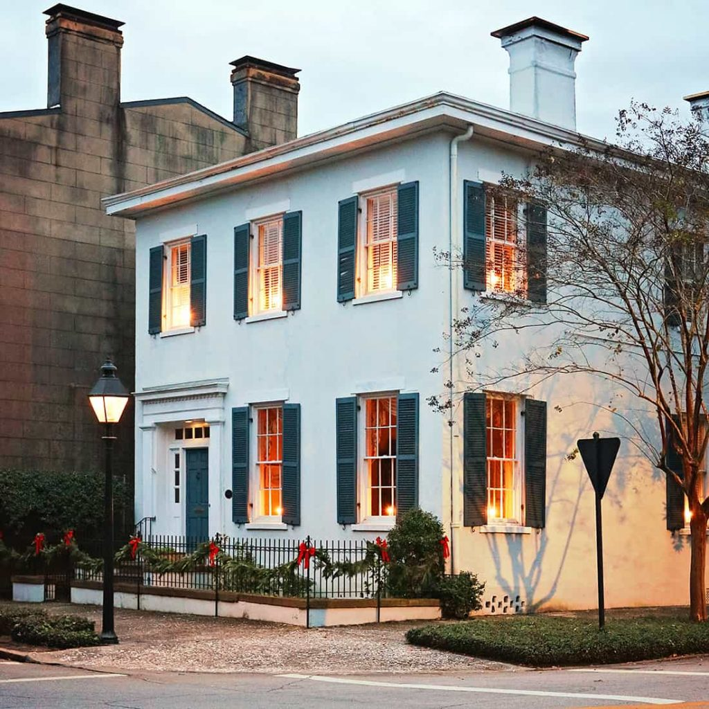 Pale blue historic home with dark blue shutters, candles illuminating the windows, and Christmas greenery on its wrought-iron fence