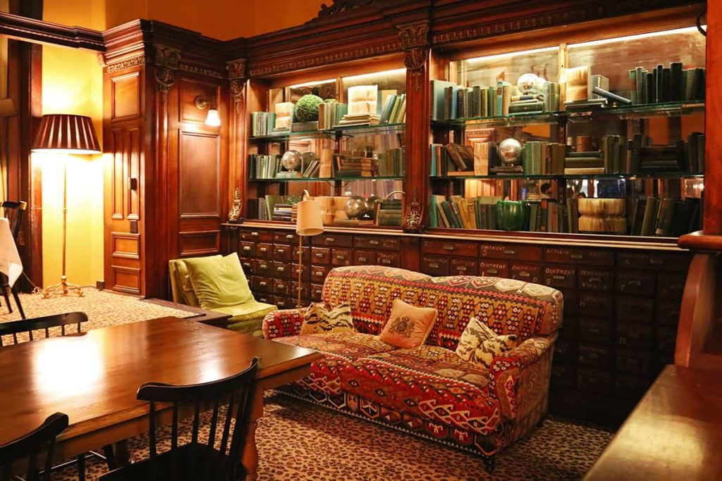 Cozy interior of Gryphon in Savannah with upholstered furniture, lamps, and bookshelves stuffed with books