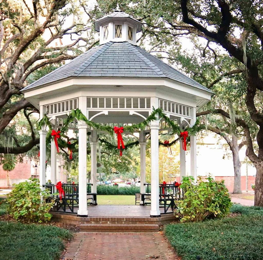 Daytime shot of the white Victorian-style gazebo in Whitefield Square, draped in Christmas greenery and red ribbon