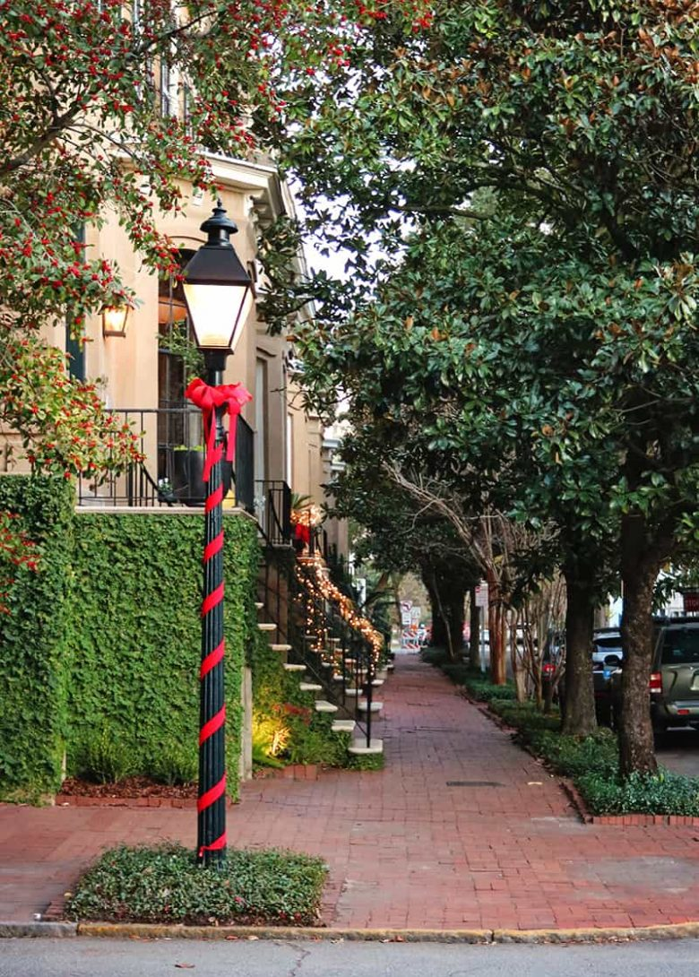 Black streetlamp wrapped in red ribbon with a red bow at the top and a view down a sidewalk lined with historic homes in Savannah