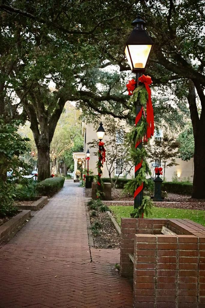 Black streetlamps in Troup Square lined with greenery and red Christmas ribbons and topped with red bows
