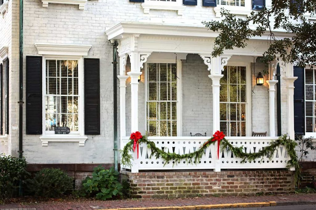 Two-story gray brick home with black shutters and a Victorian-style porch decorated with holiday greenery