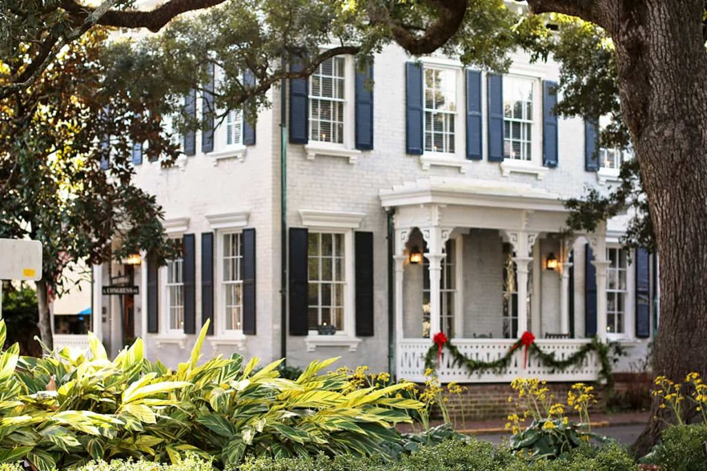 View of a two-story traditional home in Savannah decorated for Christmas, seen from a distance through a square with greenery and large oaks