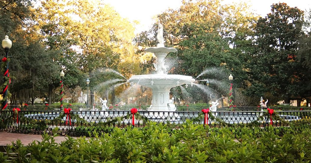The Forsyth Park fountain illuminated by sunlight with greenery and red Christmas bows decorating the lamp posts