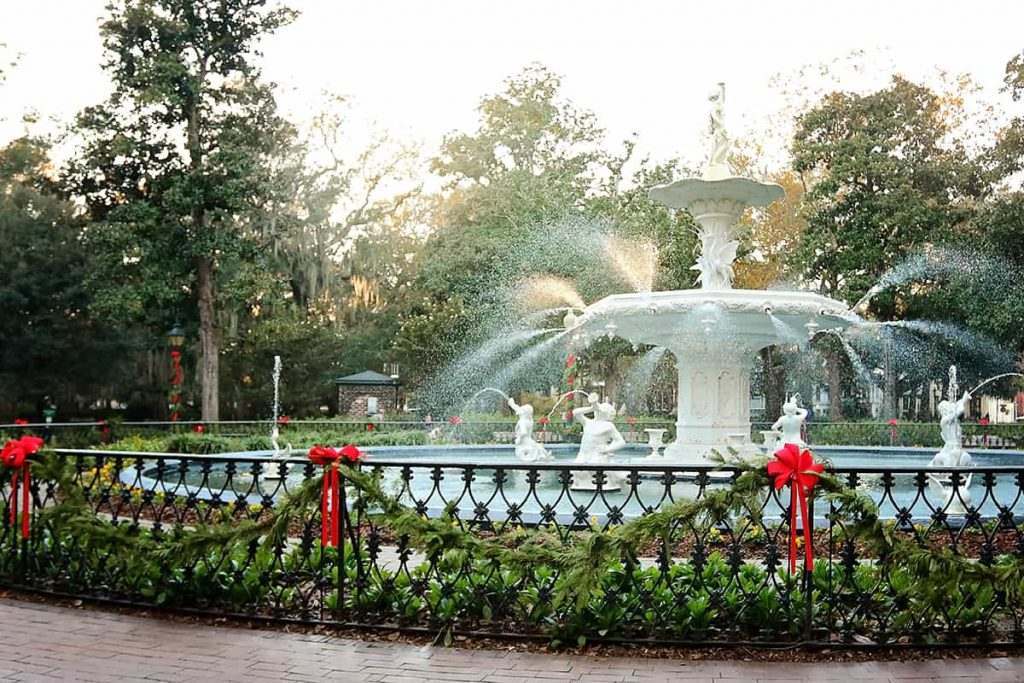 Forsyth Park fountain dressed in greenery and red Christmas ribbons with sunlight illuminating the water spraying from the fountain