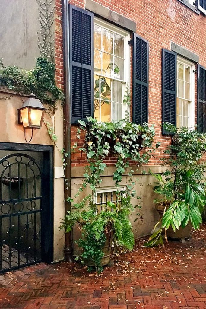 Rainy day scene of a historic brick home on Jones Street with black shutters and greenery hanging from the window boxes