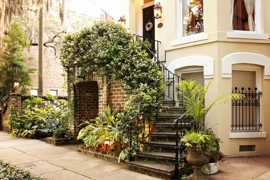 Container plants and climbing Confederate Jasmine surround the entry to a home on Jones Street