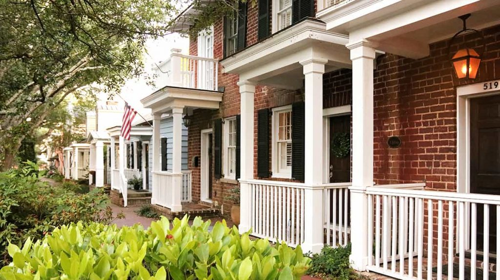 Homes with small porches and pretty landscaping on the far east end of Jones Street in Savannah GA