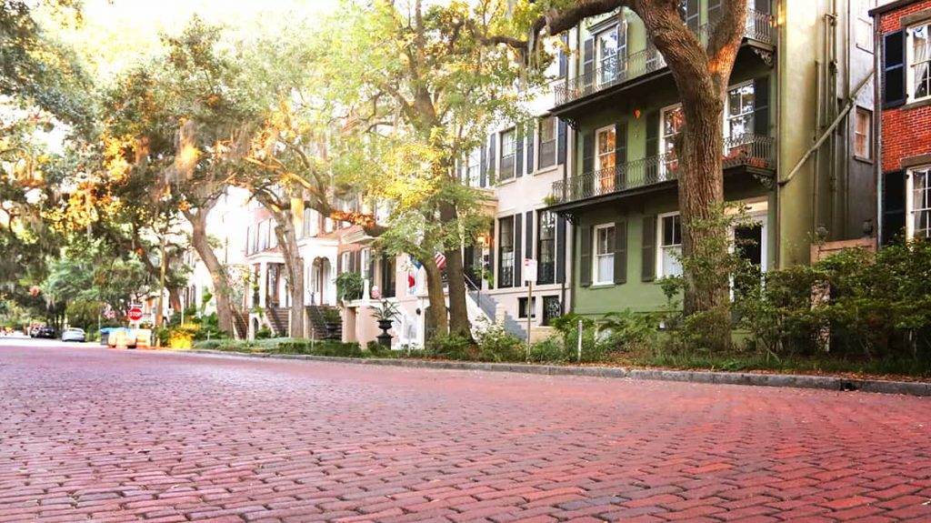 Jones Street, the prettiest street in America, with a wide expanse of brick pavers in the foreground and large homes and mature oaks in the background.