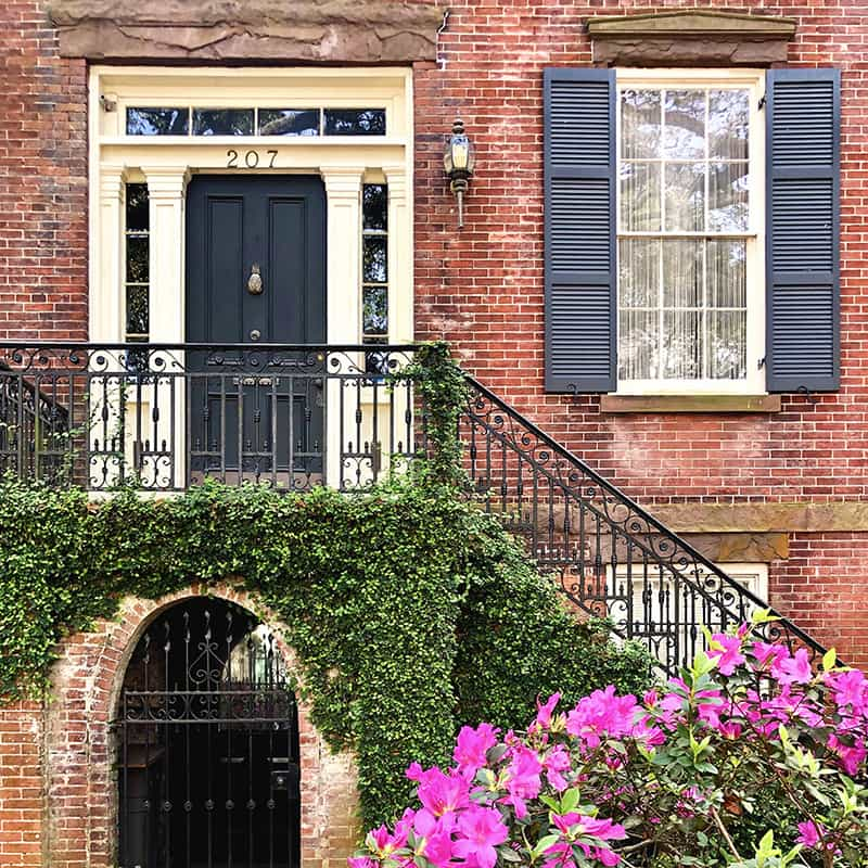 Historic brick home facade on Jones Street with hot pink azaleas blooming in the foreground