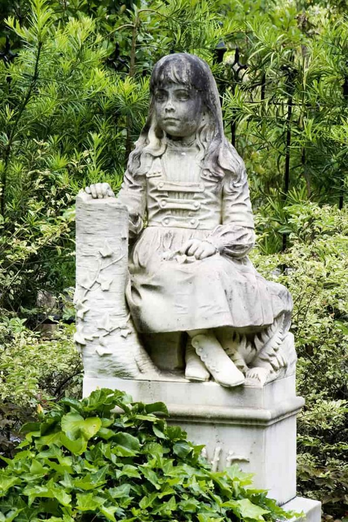 Statue of a little girl with long hair wearing a dress and sitting properly with her ankles crossed