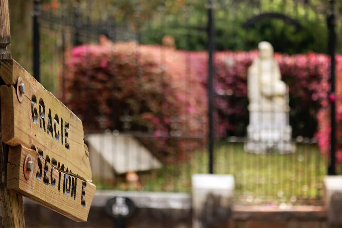 """Wooden sign with """"Gracie Section E"""" etched into it in the foreground and the grave of Little Gracie Watson in the background"""