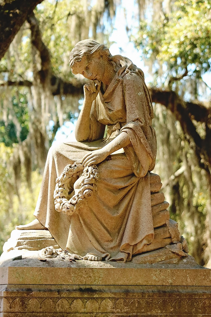Statue of a woman sitting and thinking with her head resting on her right hand and a wreath in her left hand