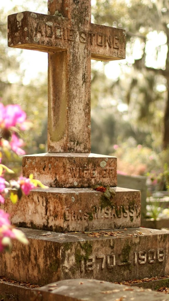 An old weathered stone cross with lichens growing on it at Bonaventure Cemetery