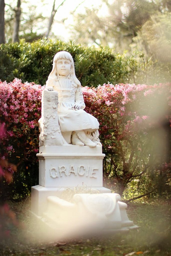 Statue of Little Gracie Watson in Bonaventure Cemetery with pink blooming flowers and greenery behind her
