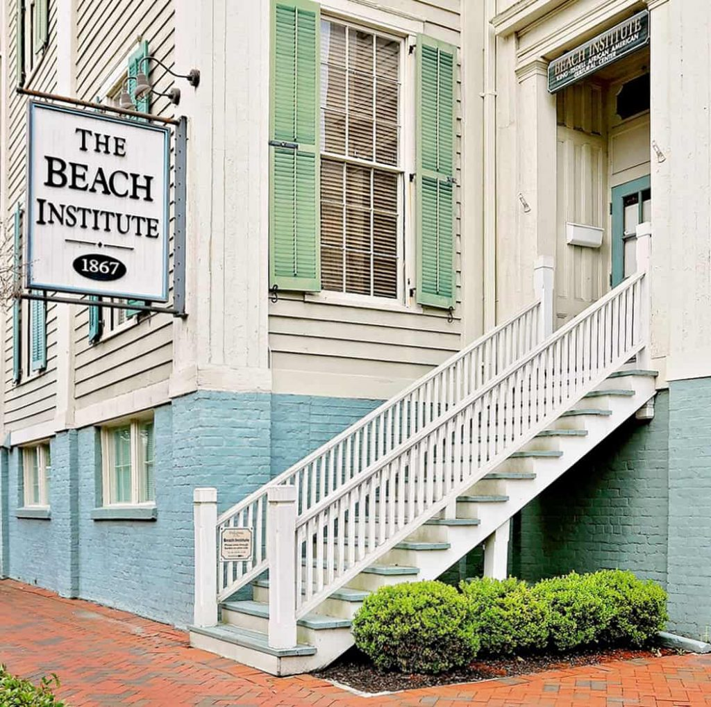 White building with green shutters and a sign that reads The Beach Institute 1867