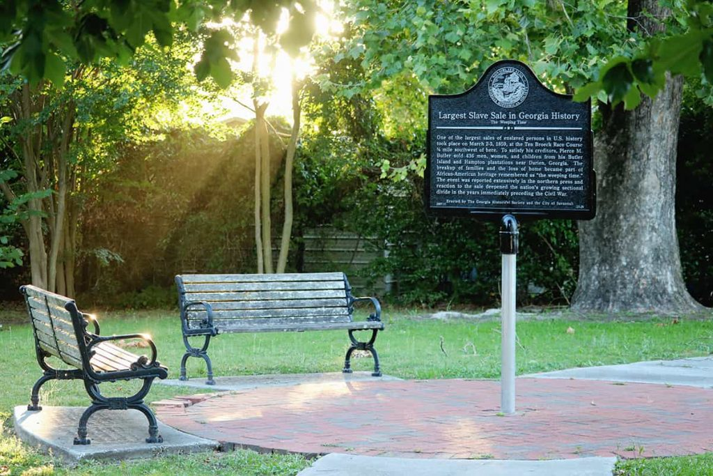 Sunlight streaming through the trees and casting a warm glow on two benches next to The Weeping Time historic marker in Savannah