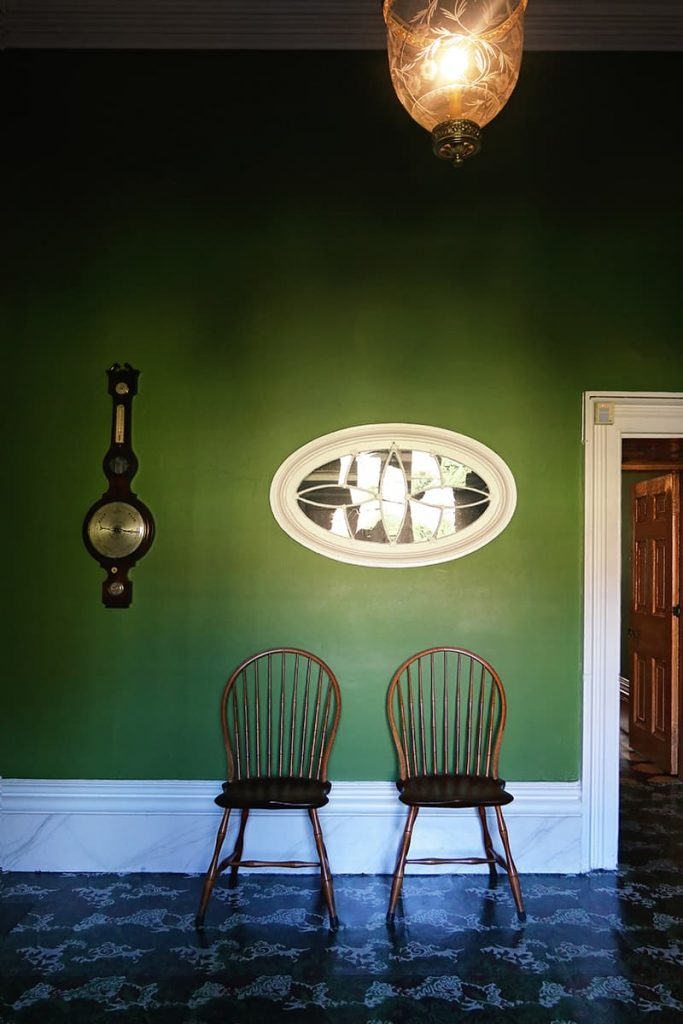 An elegant room with deep green painted walls, marble trim, and leaded glass decor