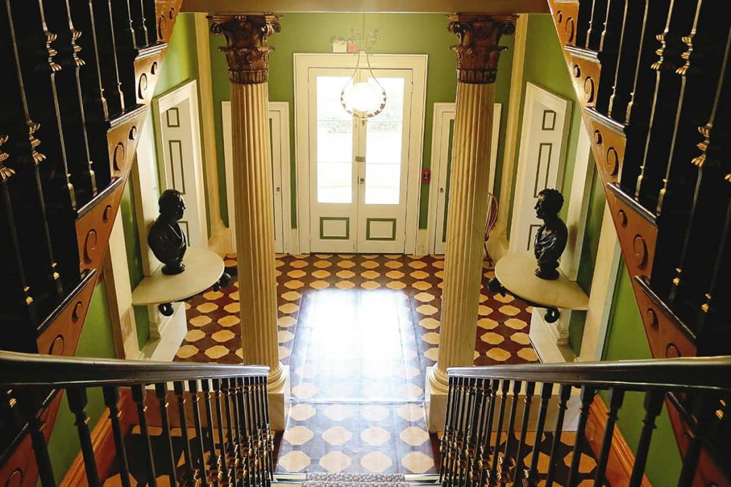 An elegant entry at the Owens-Thomas House with busts of men on tables at each side of the door