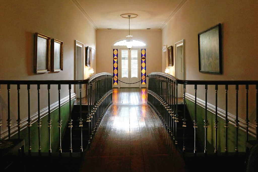 Curved bridge on the upper floor of a residence, connecting two sides of the home to one another.