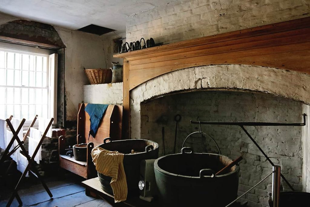 Basement of the Owens-Thomas House with a massive fireplace and large pots for laundry