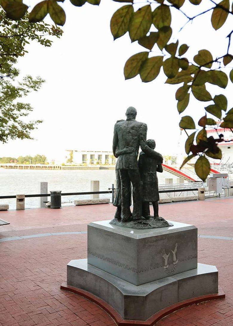 Back view of the African American Monument with a father's arms wrapped around his family as they look out towards the Savannah River