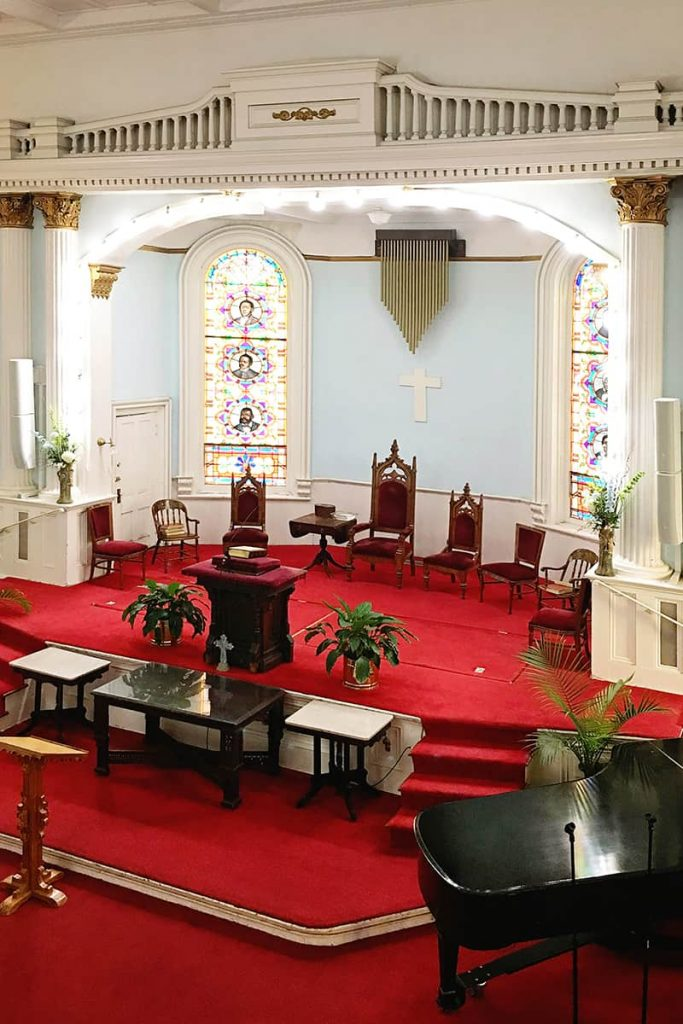 Sanctuary of First African Baptist Church with bright red carpet, pale blue walls, and a pulpit surrounded by stained glass