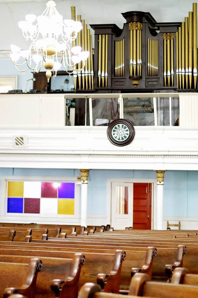 The historic First African Baptist Church choir loft and sanctuary interior with colorful stained glass and a red door