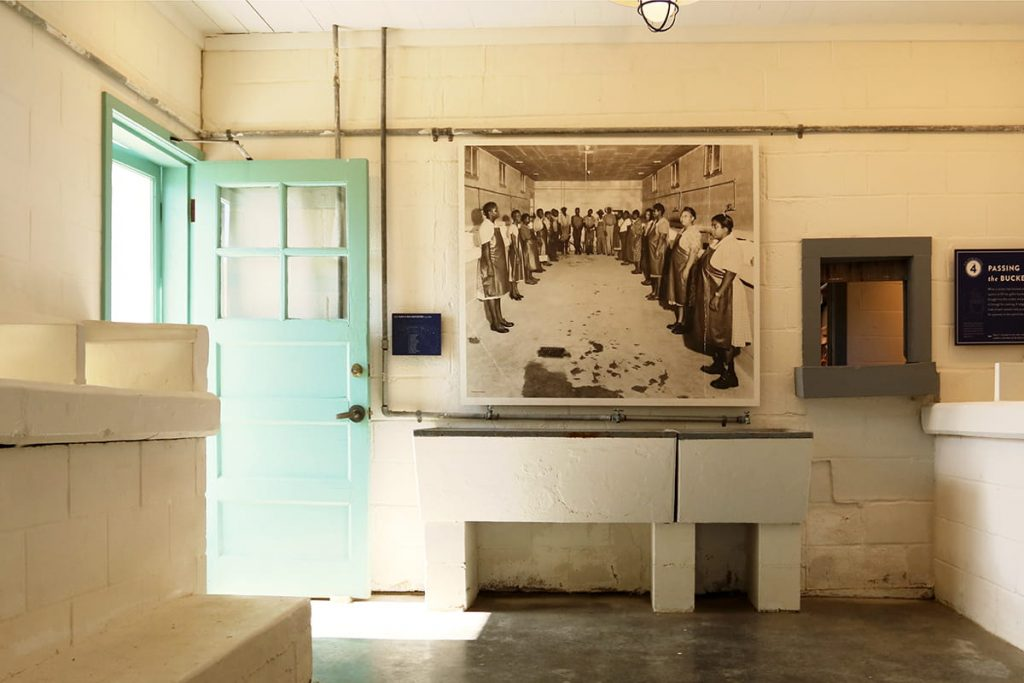 Interior of Pin Point Heritage Museum with concrete floors, a door painted Haint blue, and learning stations posted along the wall