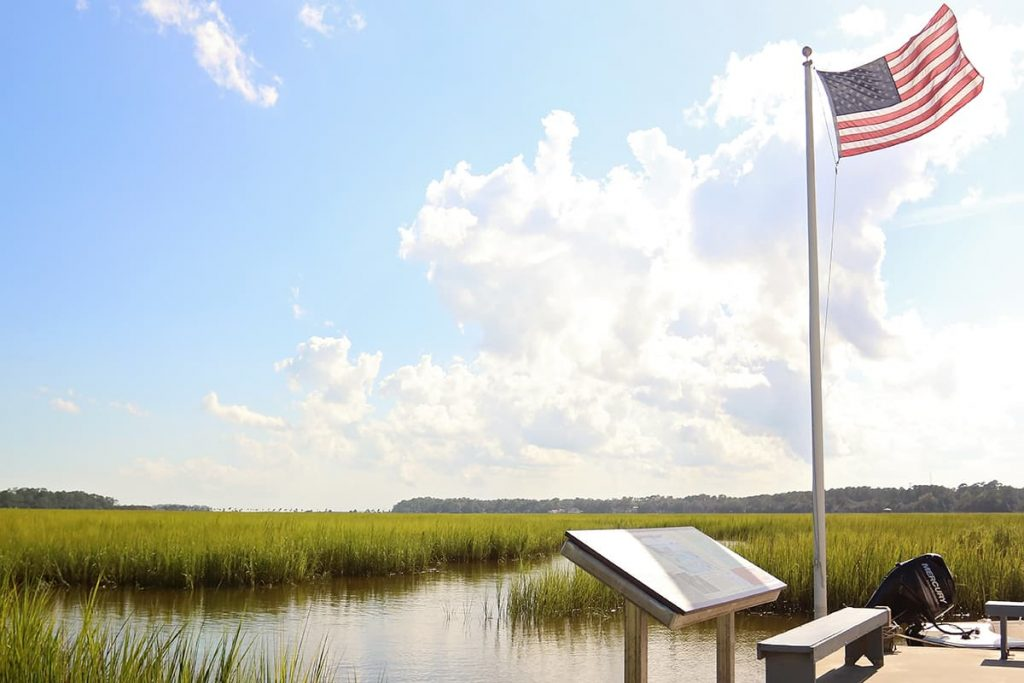 An American flag waving in the wind over the marsh views at Pin Point Heritage Museum