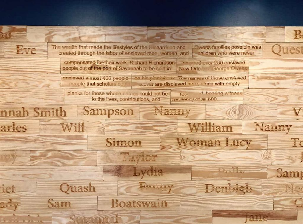 Wall made from wooden planks, some with names burned into them and some blank. Each plank honors an enslaved person who worked for the Owens family