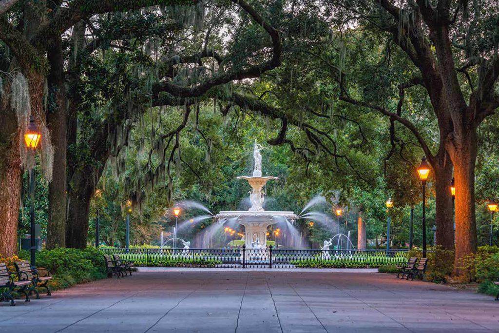 Forsyth Park fountain at dusk surrounded by gas-lit lamps and trees covered in Spanish moss